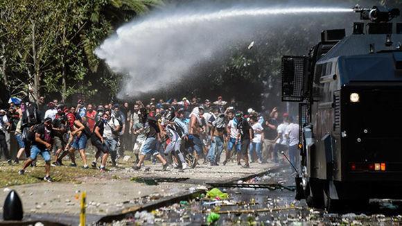 Un camión hidrante embiste a los manifestantes frente al Congreso. Foto: AFP.