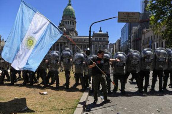 Un manifestante se para con una bandera argentina frente al cordón policial. Foto: AFP.