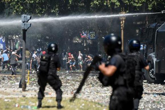 Los policías avanzan hacia Avenida de Mayo, mientras los manifestantes se repliegan. Foto: AFP.