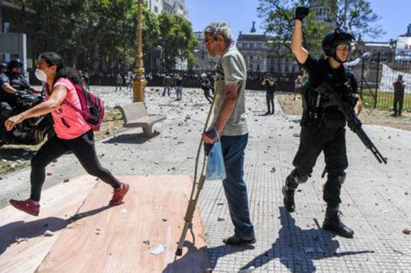 Un hombre con muletas, en medio de un policía y un manifestante. Foto: AFP.