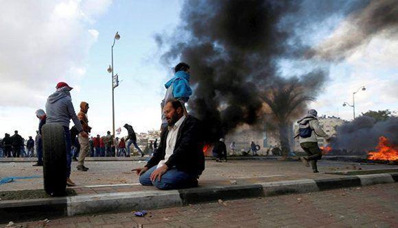 Un manifestante palestino reza durante los enfrentamientos con las tropas israelíes en una protesta contra la decisión del presidente estadounidense Donald Trump de reconocer a Jerusalén como la capital de Israel, cerca del asentamiento judío de Beit El, cerca de la ciudad cisjordana de Ramallah. Foto:Reuters.