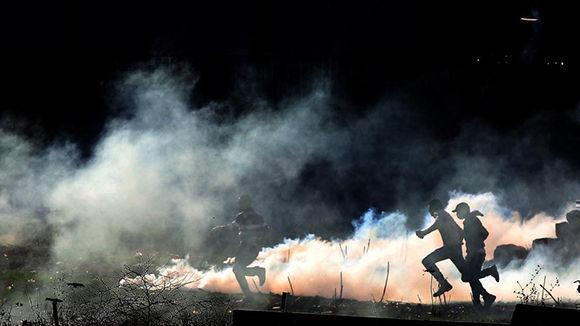 Palestinos corren para protegerse de una granada de gas lacrimógeno lanzada por el ejército israelí durante unos disturbios en Qusra, cerca de Nablus esta semana. Foto: Alaa Badarneh / EFE.
