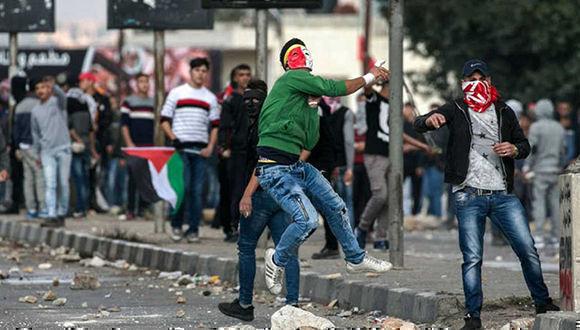 Un manifestante palestino arroja piedras durante los enfrentamientos con las fuerzas de seguridad israelíes cerca del puesto de control de Huwara. Foto: AFP