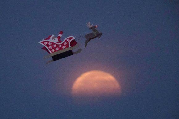 Una figura de Santa Claus de control remoto vuela cerca de la Superluna en Carlsbad, California (EE UU), el 3 de diciembre de 2017. Foto: Mike Blake /Reuters