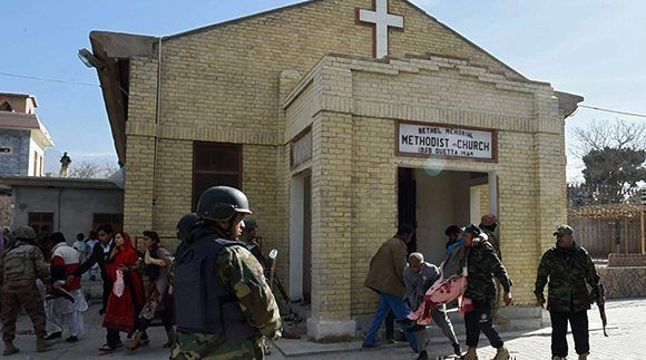 Agentes de seguridad pakistaníes aseguran el exterior de la iglesia. mientras sacan a los heridos. Foto: AFP.
