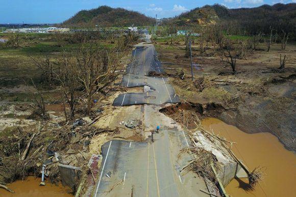 Un hombre monta en bicicleta por una calle destrozada en Toa Alta, al oeste de San Juan (Puerto Rico) el 24 de septiembre de 2017, tras el paso del huracán María. Foto: AFP/Getty Images