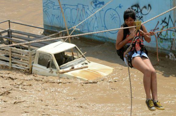 Los habitantes del distrito de Huachipa, al este de Lima (Perú), son ayudados por los equipos de rescate de policías y bomberos a cruzar al otro lado de la calle debido a las inundaciones que dejaron aislados a los residentes. Foto: Getty Images.