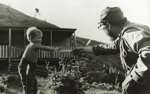 Fidel le ofrece una barra de chocolate a hijo de campesinos en la Sierra Maestra, 1958. Fuente: Oficina de Asuntos Históricos / Sitio Fidel Soldado de las Ideas.
