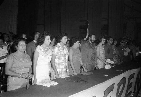Fidel Castro junto a Vilma Espín y Gilberto Cervantes, presidente de la Cruz Roja Cubana, en el acto de fundación de la Federación de Mujeres Cubanas (FMC) en el teatro Lázaro Peña en La Habana, 23 de agosto de 1960. Foto: Tirso Martínez / Sitio Fidel Soldado de las Ideas