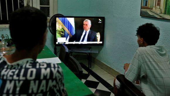 Dos jóvenes ven la entrevista al presidente cubano, Miguel Diaz-Canel, de la cadena de televisión TeleSur, en La Habana. Foto: EFE/Ernesto Mastrascusa