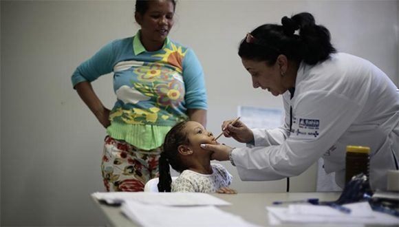 Una doctora cubana examina a una pequeña paciente. Foto: Reuters.