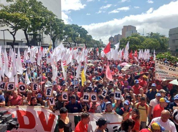 """""""Manos fuera de Venezuela"""", se lee en inglés en el cartel que alzan los caraqueños que encabezan la marcha. Foto: Noticias24"""