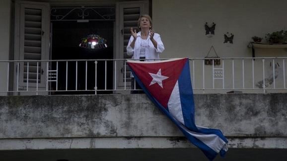 Una mujer cubana aplaude desde su balcón en La Habana como celebración por el Día Internacional de los Trabajadores. Foto: Ismael Francisco / AP