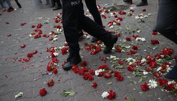 Policías de Turquía caminan por encima de las flores que dejaron los manifestantes durante las protestas en Estambul en el Día de los Trabajadores. Foto: Emrah Gurel / AP