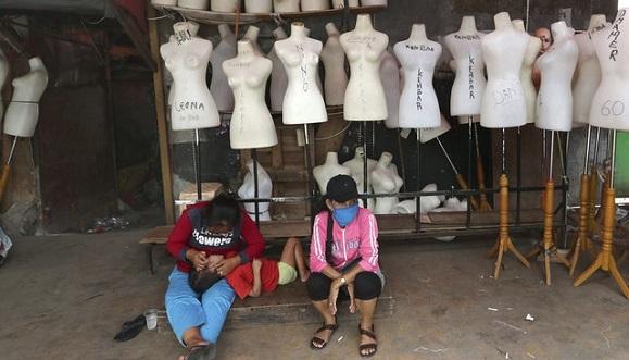 Mujeres de Indonesia se sientan junto a maniquís cerca de una fábrica textil. Foto: Tatan Syuflana / AP