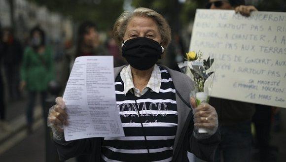 Una señora sostiene la flor Lirio del Valle durante una concentración en el Día Internacional de los Trabajadores en Marsella, Francia. Foto: Daniel Cole / PA