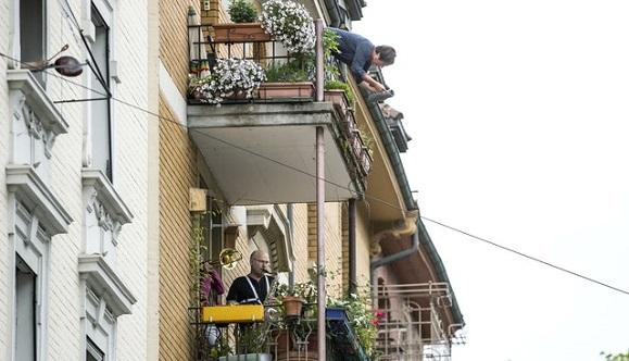 Las personas tocan instrumentos musicales desde sus balcones, en Zúrich, Suiza, en el Día Internacional de los Trabajadores. Foto: Alexandra Wey / AP
