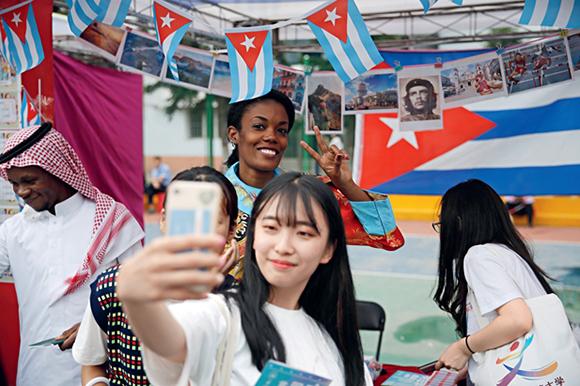 Una joven se toma una foto frente al stand de Cuba en el primer Festival Cultural Internacional de la Universidad Normal de Harbin, el 13 de junio de 2019. Foto: CNS Phot.