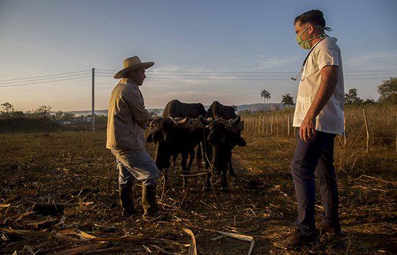 En su recorrido de pesquiza epidemiológica, Gabriel habla con Luis Figueroa, campesino del municipio La Palma, en Pinar del Río. Foto: Ismael Francisco/ Cubadebate.