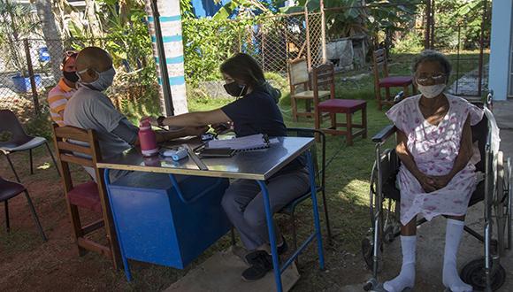 Patrica Real Alfonso, estudiante de Medicina, le toma la tensión arterial a los pacientes, después de ser vacunados con Abdala, en el Consultorio #17 de Río Verde, Boyeros, La Habana. Foto: Ismael Francisco/ Cubadebate.